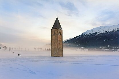 The sunken church tower in the Reschensee lake in wintertime